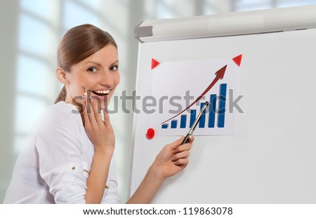 Smiling woman pointing at the business progress chart, office background - stock photo