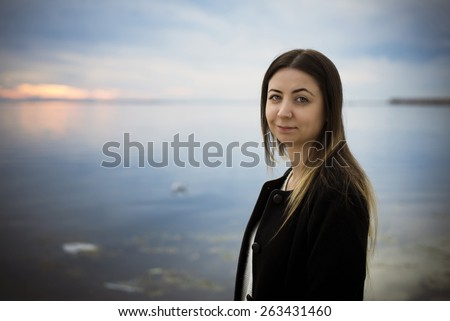 Smiling woman portrait against sea and moody sky. - stock photo
