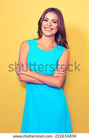 smiling woman portrait . female model in blue dress against yellow background. - stock photo