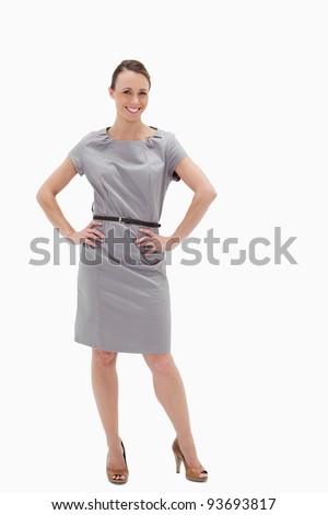 Smiling woman posing in a dress with her hands on her hips against white background
