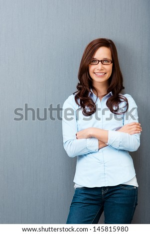 Smiling woman posing with glasses over the grey background - stock photo