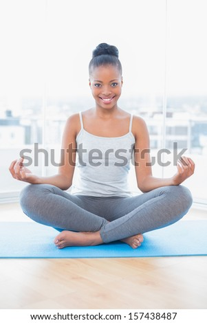 Smiling woman practicing yoga while looking at camera in bright room at home