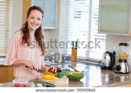 Smiling woman preparing salad in the kitchen - stock photo