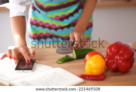 Smiling woman preparing salad in the kitchen, isolated - stock photo