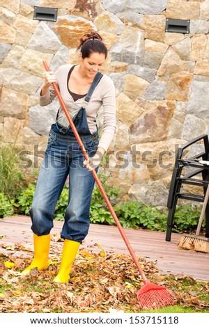 Smiling woman raking leaves autumn fall garden housework - stock photo
