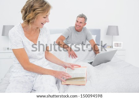 Smiling woman reading book while husband is using laptop in bedroom at home - stock photo
