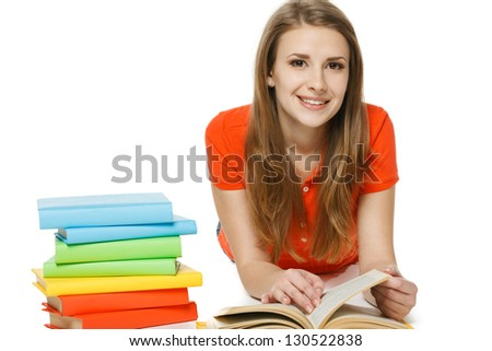 Smiling woman reading the book lying on the floor, looking at camera, over white background