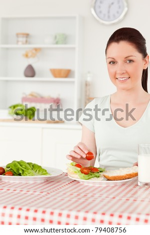 Smiling woman ready to eat a sandwich for lunch in her kitchen