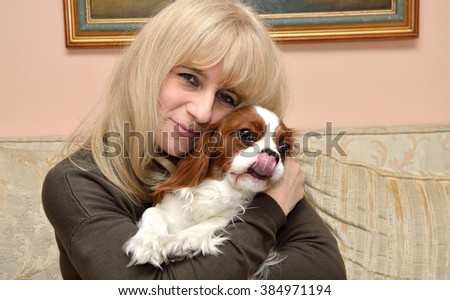 Smiling woman relaxing and hugging her dog, Cavalier King Charles Spaniel (Blenheim) - stock photo