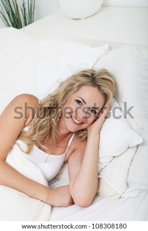 Smiling woman relaxing in bed High angle view of a beautiful young smiling woman relaxing amongst the pillows on her bed - stock photo