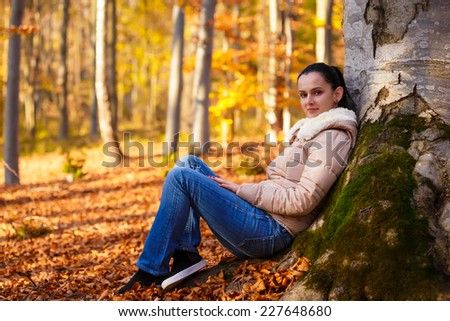 Smiling woman relaxing in nature while autumn season - stock photo
