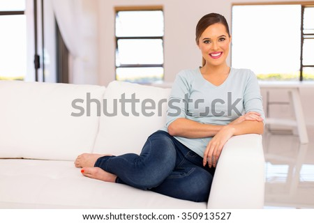 smiling woman relaxing on a couch at home