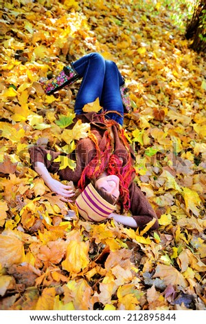 Smiling woman resting on autumn leaves in park.  - stock photo