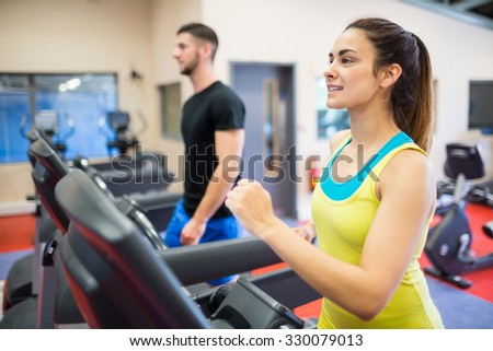 Smiling woman running on a treadmill at the gym