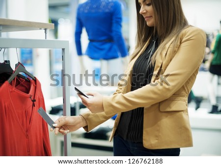 Smiling woman scanning QR code on smart phone - stock photo