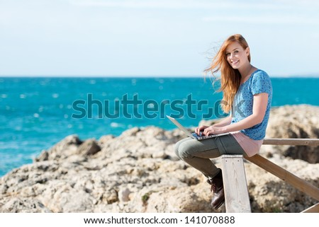 Smiling woman sending emails at the seaside sitting on a wooden rail overlooking the ocean with her computer balanced on her knees - stock photo