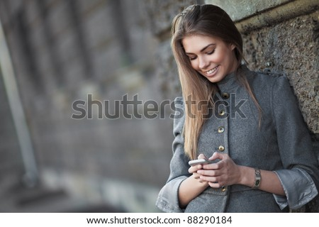 Smiling woman sending sms on the street - stock photo