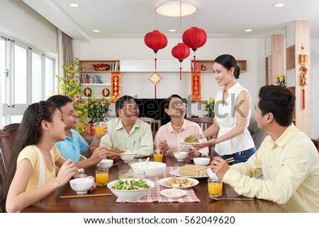 Smiling woman serving family dinner for Tet celebration; couplets with best wishes for coming year in the background