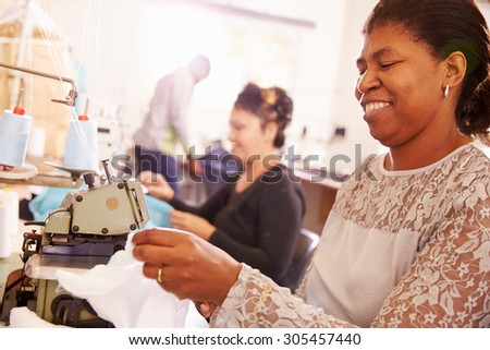 Smiling woman sewing at a community workshop, South Africa - stock photo