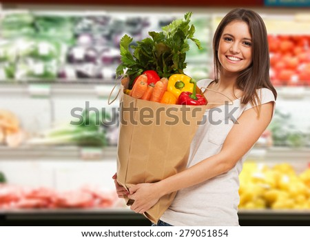 Smiling woman shopping in a supermarket - stock photo