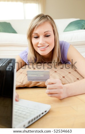 Smiling woman shopping on-line lying on the floor at home - stock photo