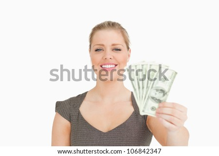Smiling woman showing dollars banknotes against white background
