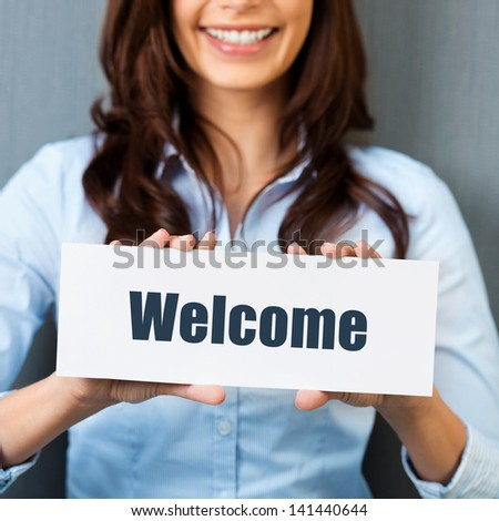 Smiling woman showing white card with welcome word in a close up shot - stock photo