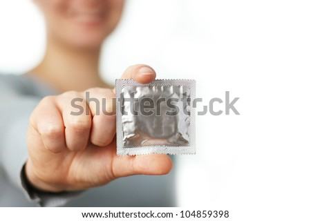 smiling woman shows a condom - stock photo