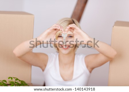 smiling woman shows house key forming a heart - stock photo