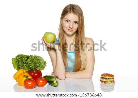 Smiling woman sitting between healthy food and fast food and holding green apple, over white background - stock photo