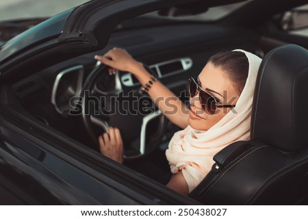 Smiling woman sitting in car, Happy girl driving automobile, outdoors summer portrait.  Young woman driving on road trip on beautiful sunny summer day.Portrait sexy fashion woman model in sunglasses