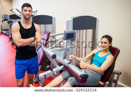 Smiling woman sitting in the weights machine at the gym - stock photo