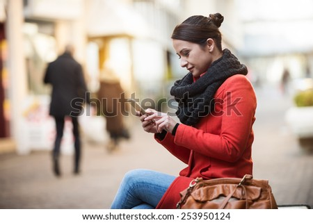 Smiling woman sitting on a bench in a city street and using her smart phone - stock photo