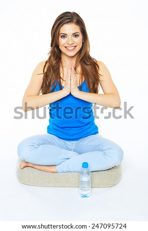 Smiling woman sitting on a floor with crossed legs. Water bottle. Yoga pose. - stock photo