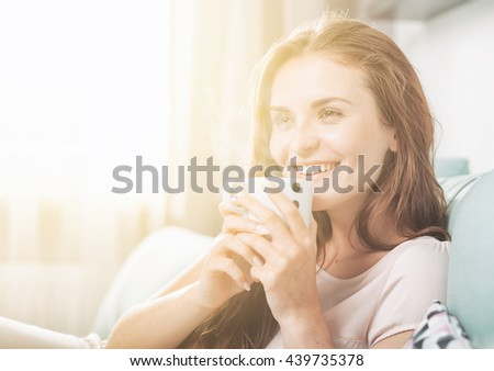 Smiling woman sitting on couch at home and drinking coffee, casual style indoor shoot - stock photo