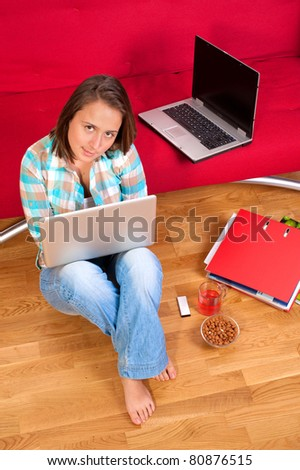 Smiling woman sitting on floor at home in living room using her laptop - stock photo