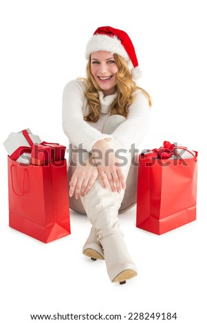 Smiling woman sitting on floor with shopping bag on white background