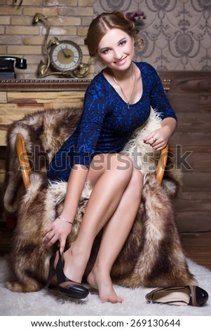 Smiling woman sitting on the chair and removing her shoes - stock photo