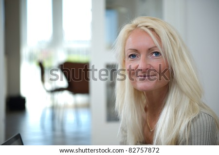 Smiling woman sitting on the floor with here laptop