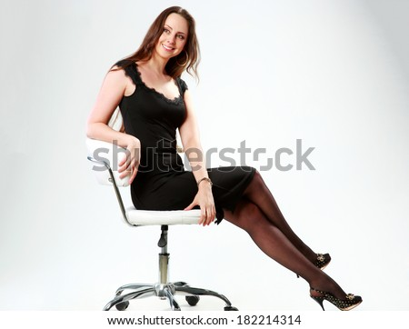 Smiling woman sitting on the office chair and looking away over gray background - stock photo