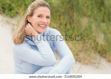Smiling woman sitting on the sand at the beach