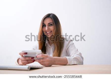 Smiling woman sitting on the table and using smartphone