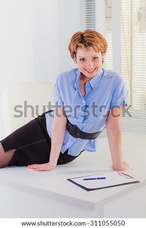 Smiling woman sitting on white desk nearby window