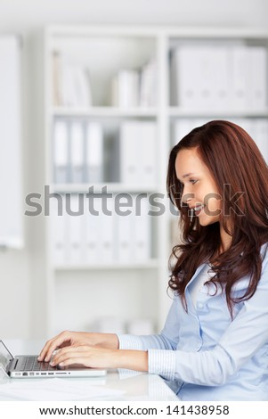 Smiling woman sitting thinking in an office chair as she mulls over a new idea in her mind - stock photo