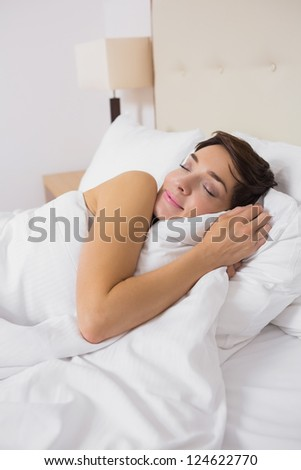 Smiling woman sleeping comfortably in bed in hotel room - stock photo