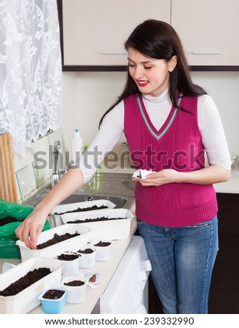 Smiling woman sowing seeds at table in home kitchen