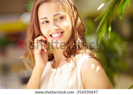 Smiling woman speaking on cellular phone on sunny day