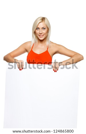Smiling woman standing behind and holding a white blank billboard / placard, over white background