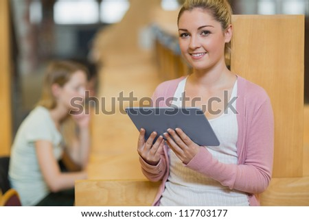 Smiling woman standing in library with tablet pc beside study desks