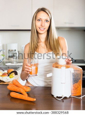 Smiling woman standing in the kitchen with a glass of freshly squeezed carrot juice - stock photo